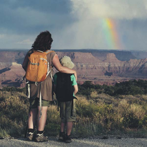 Father and son hiking by rainbow