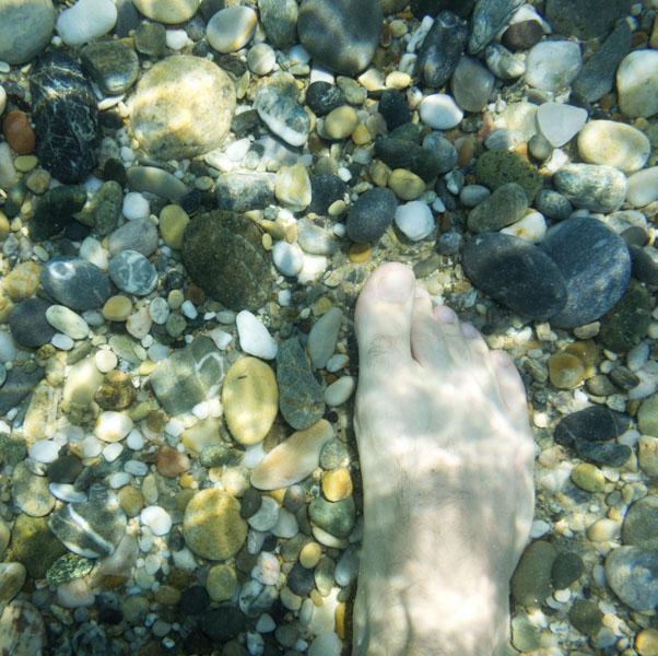 Foot walking on pebbles in lake