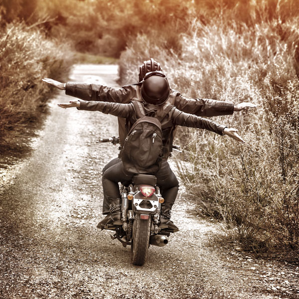 Friends on motorcycle with arms wide