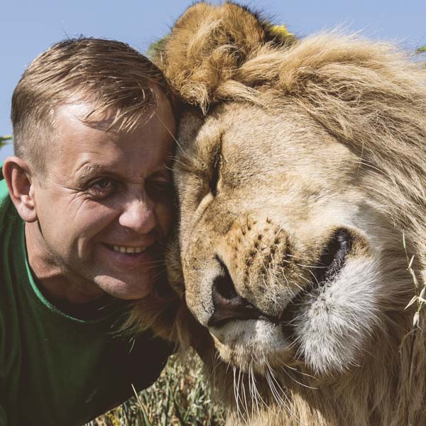 Man and lion snuggle