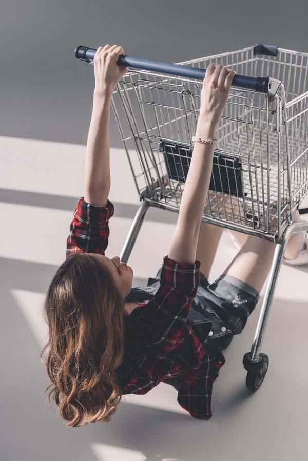 Woman hanging on shopping cart