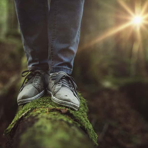 Man balancing on moss-covered log