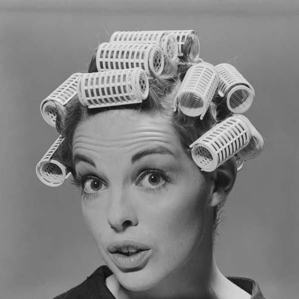 Surprised retro woman in hair curlers