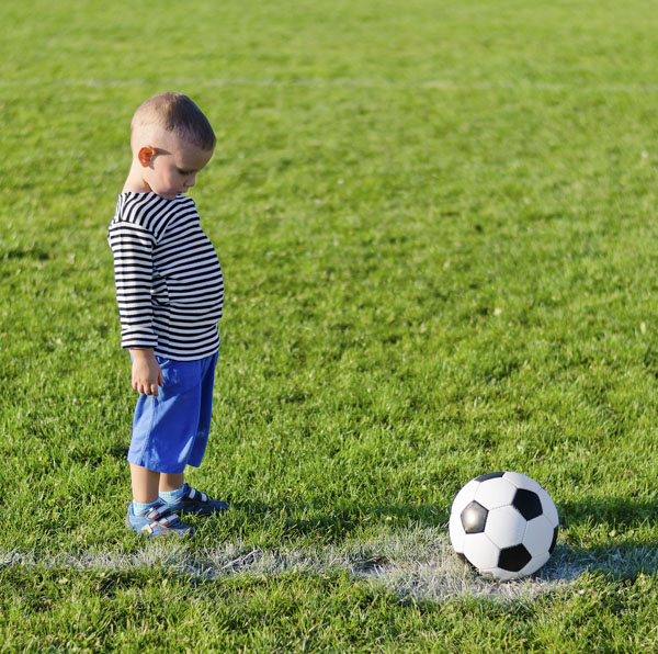 Shy little boy looking at soccer ball