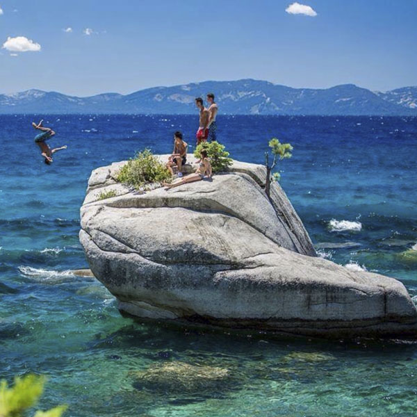Friends jumping off rock into Lake Tahoe
