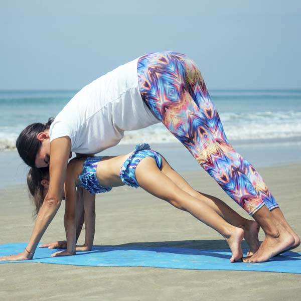 Mother and daughter in yoga pose on the beach