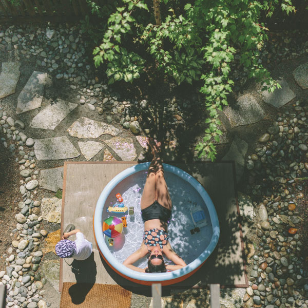 Woman relaxing in backyard inflatable pool