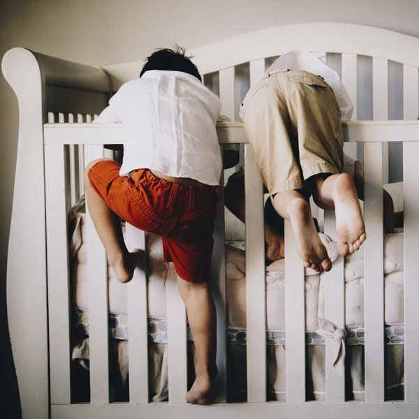 Adventurous little boys climbing into crib