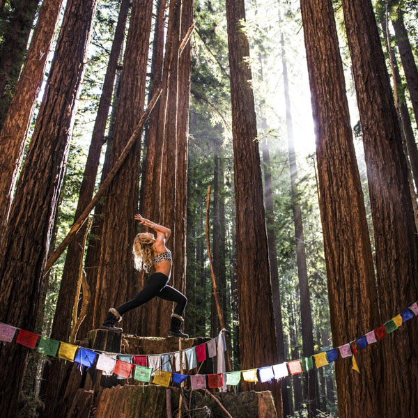 Woman doing yoga on stump in the middle of forest draped in prayer flags
