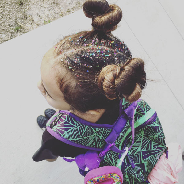 Girl wearing backpack with two hair buns and glitter in her hair