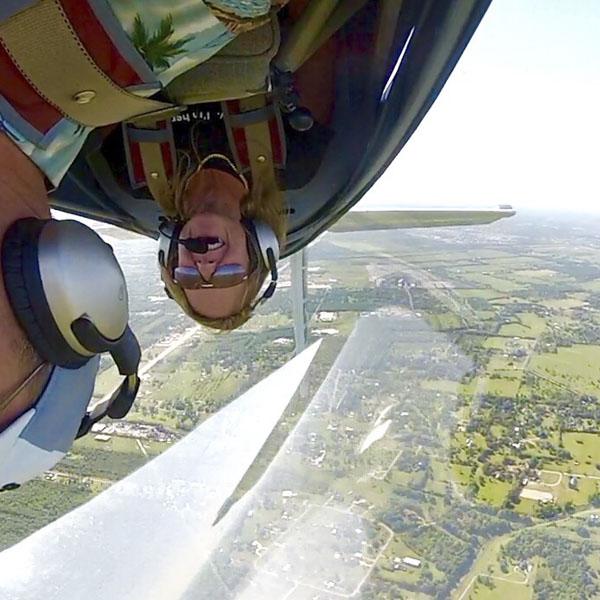 Man flying upside down in airplane