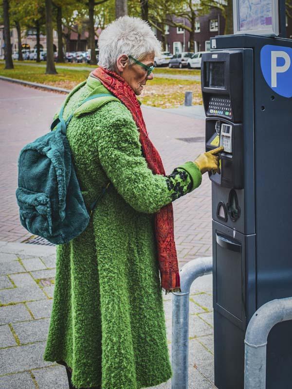 Mature spectacular woman feeding money to parking meter
