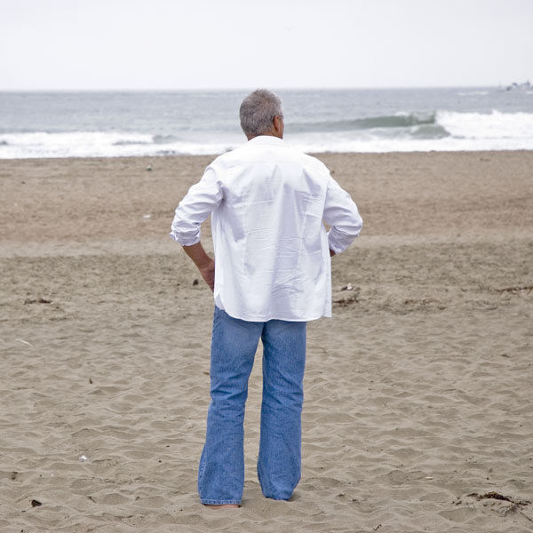 Man on beach looking out at waves