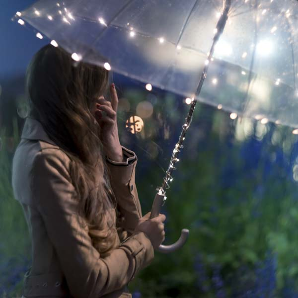 Woman carrying umbrella covered in twinkle lights
