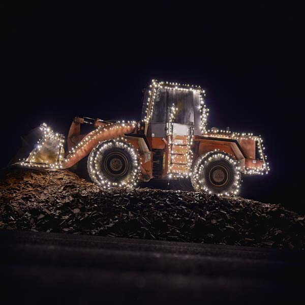 Dirt moving tractor covered in Christmas lights