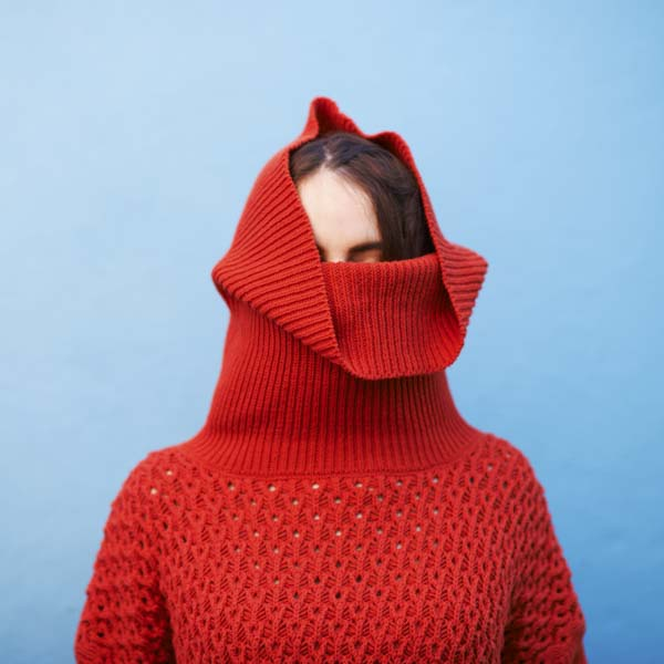 Woman with red sweater up over her head