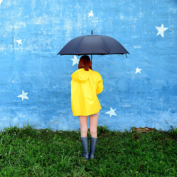 Woman with umbrella looking at stars painted on wall