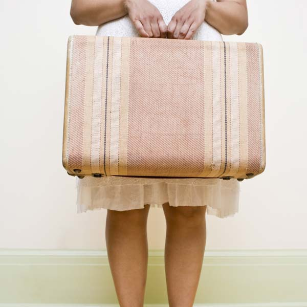 Woman holding pink suitcase