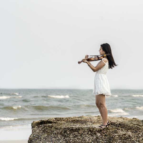 Woman playing the violin at the beach