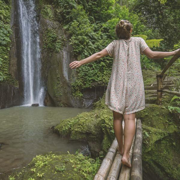 Woman walking by waterfall
