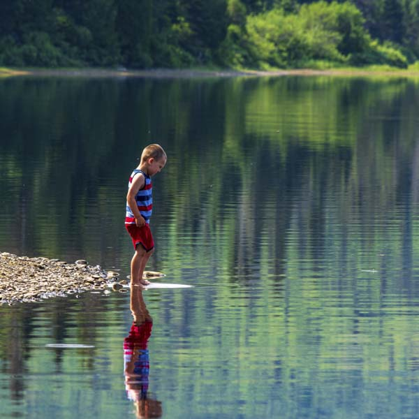 Boy looking at his reflection in a beautiful lake