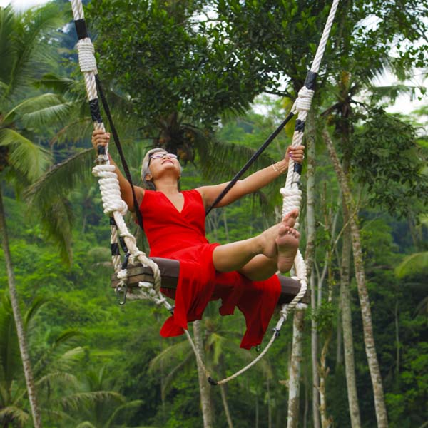Woman in red dress happily swinging on giant tree swing