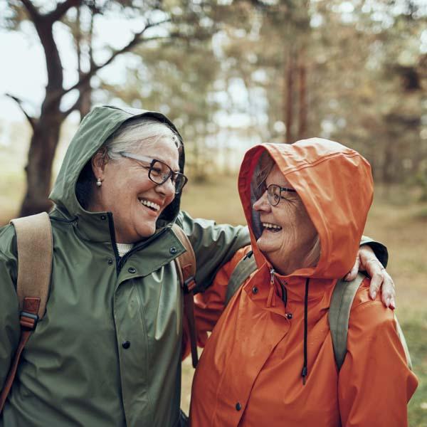 Two women hugging in rain coats