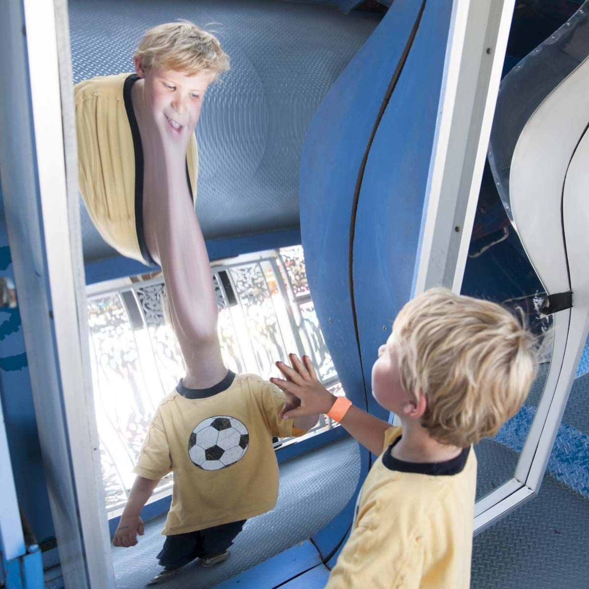 Little boy smiling at his reflection in a Fun House mirror