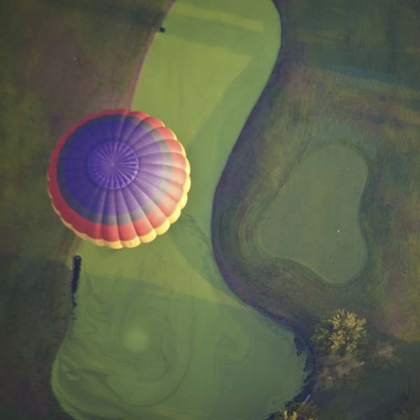 Hot air balloon floating over green