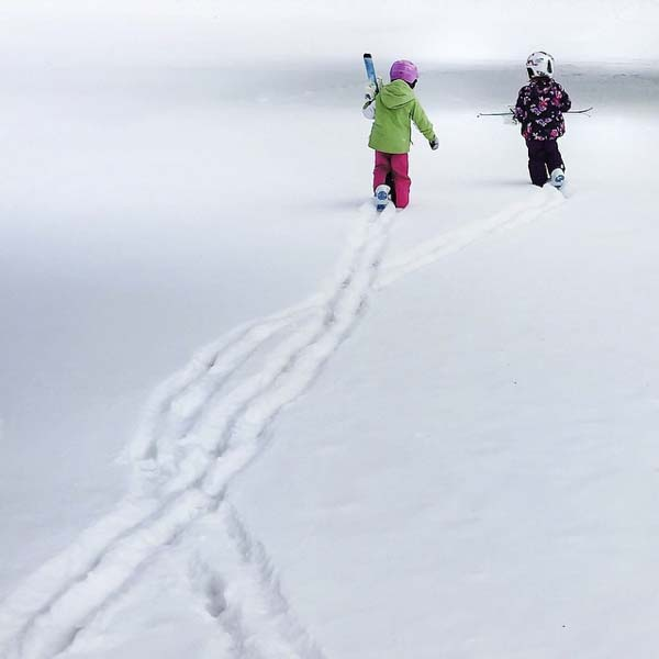 Two little snowboarders in fresh snow