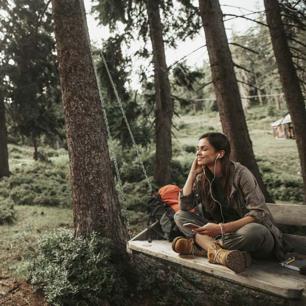 Woman listening to music on forest swing