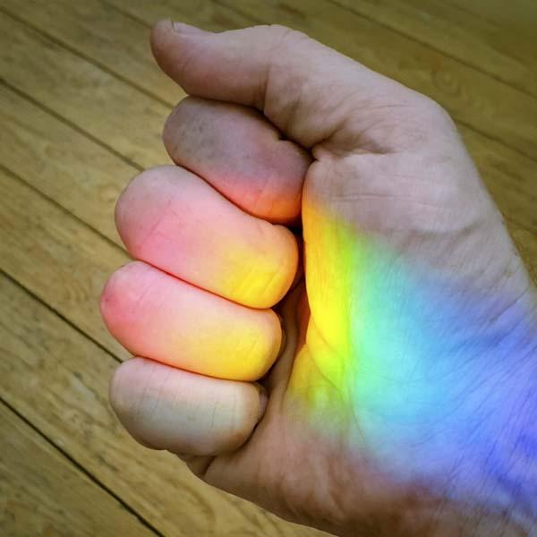 Hand grasping rainbow