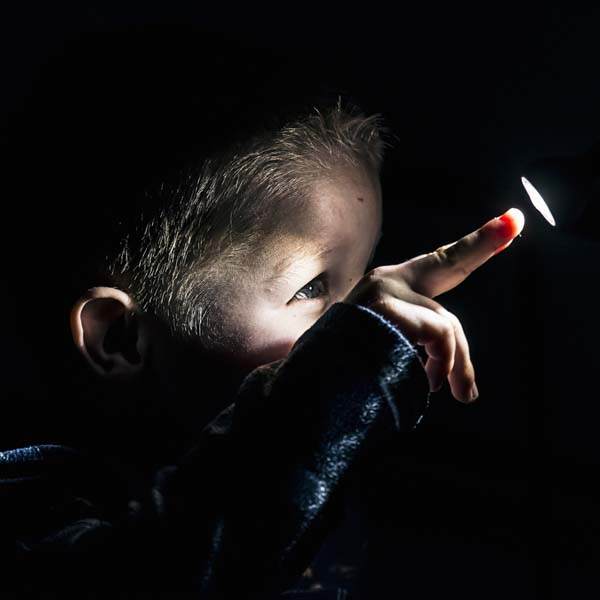Little boy poking his finger into a beam of light