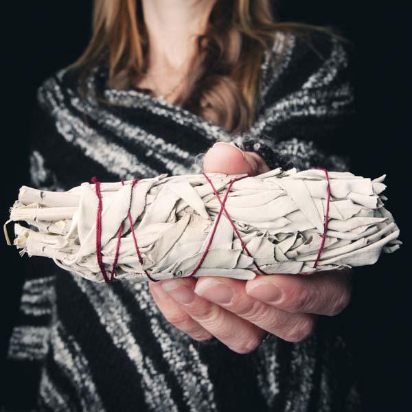 Woman holding white sage smudge stick