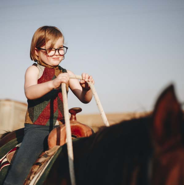 Little girl learning how to ride a horse