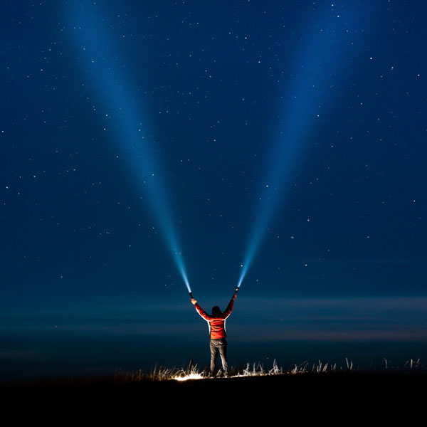 Man with two flashlights shining up to sky