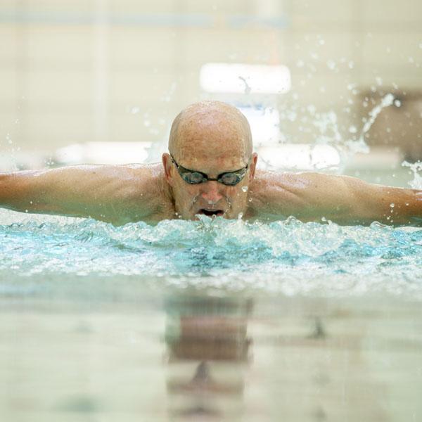 Fierce elderly man doing butterfly stroke in the pool