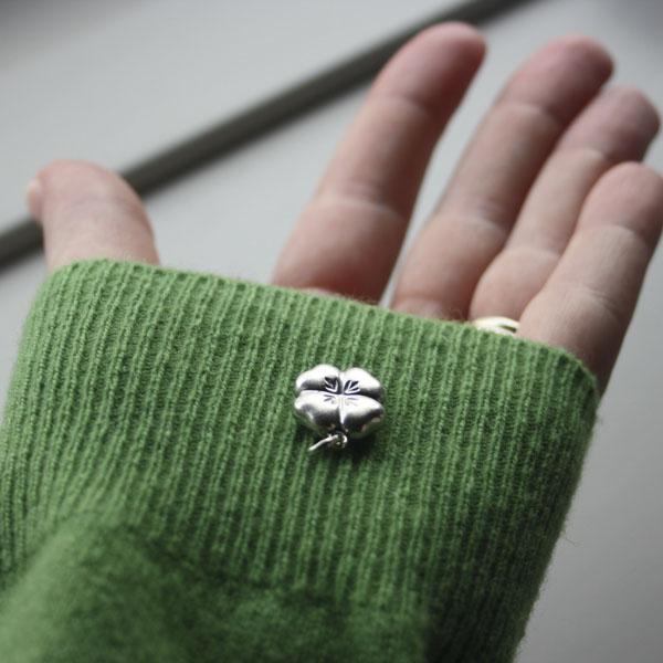 Hand holding four-leaf clover