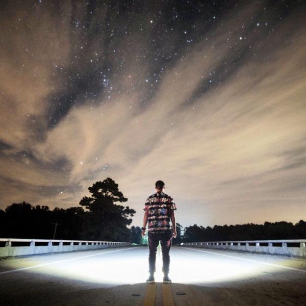 Man standing under stars on highway