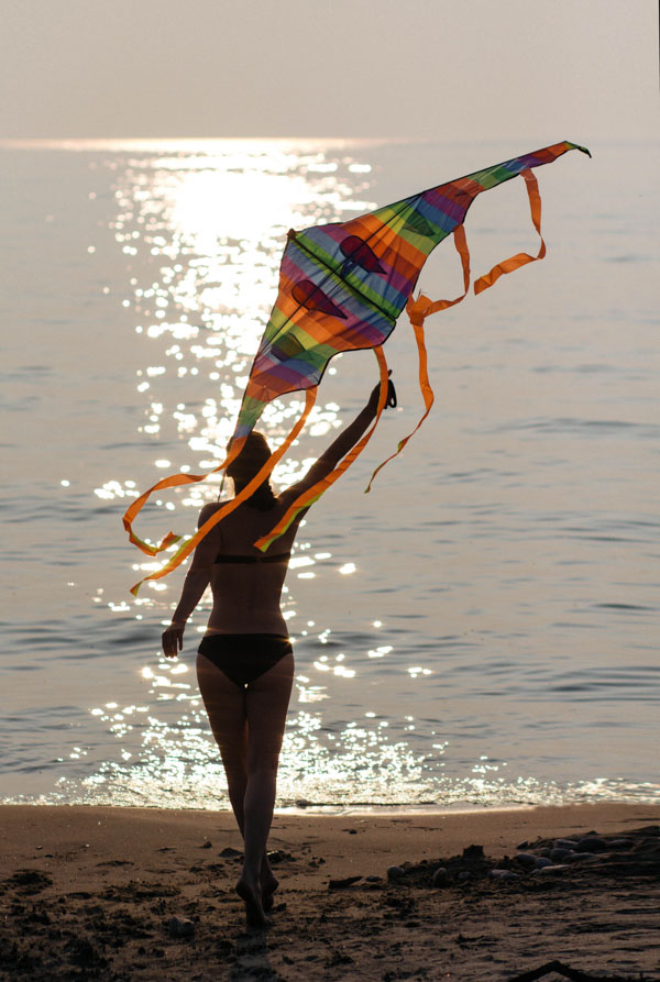 Woman with a kite at the beach