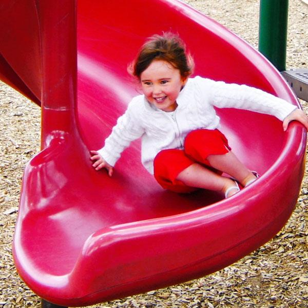 Little girl sliding down red slide