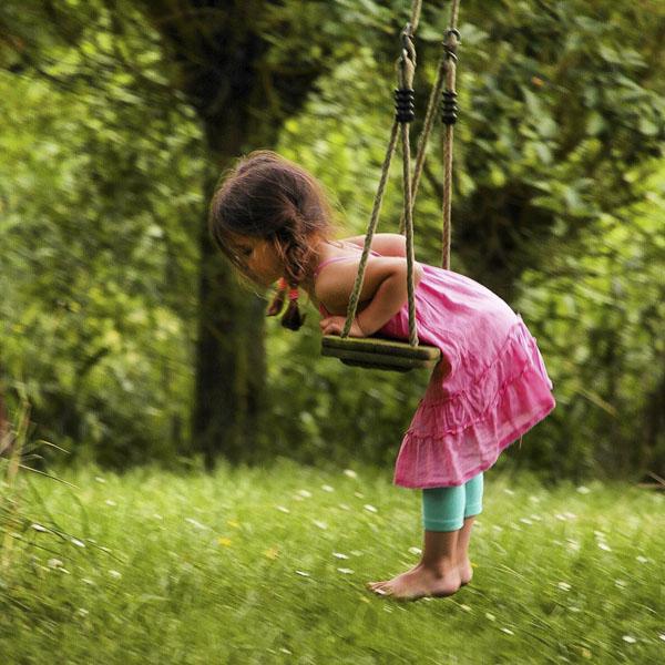 Little girl climbing onto swing