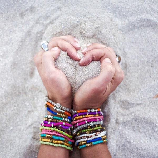 Woman gathering sand to make heart