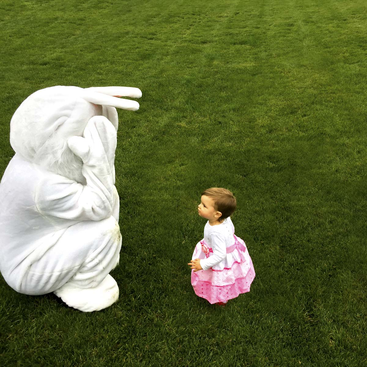 Easter bunny playing peek a boo with a child