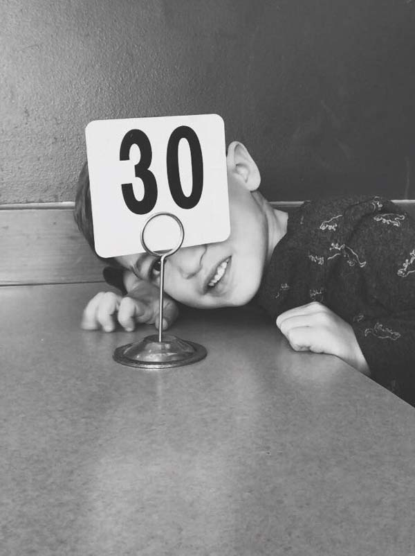 Little boy with number waiting for pizza