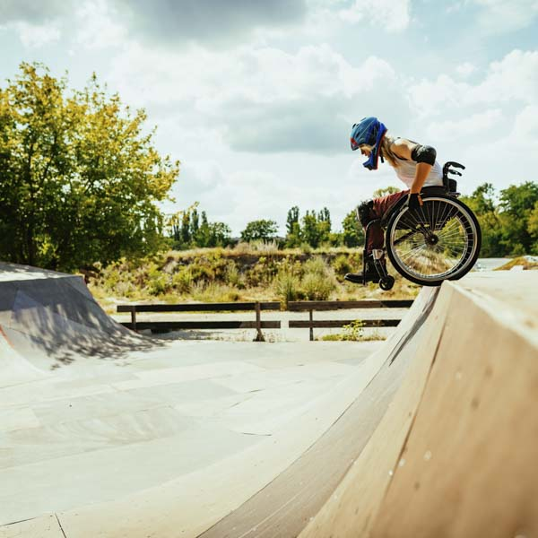 Woman in wheelchair getting ready to drop in at skateboard park