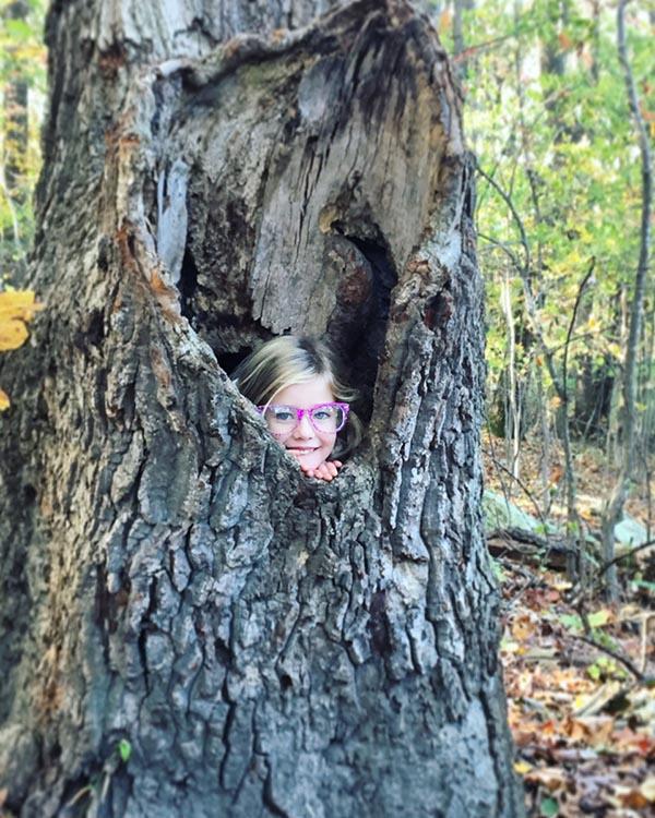 Girl peeking out of tree