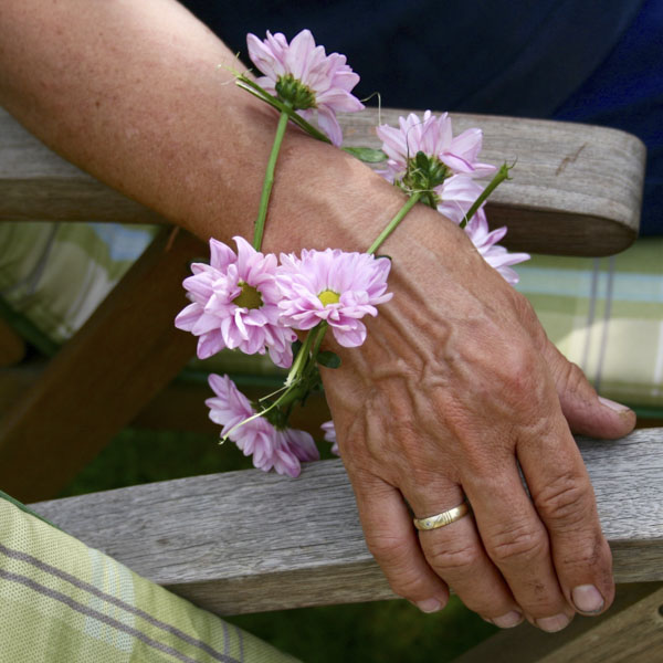Senior woman in lawn chair wearing flower ring on her wrist