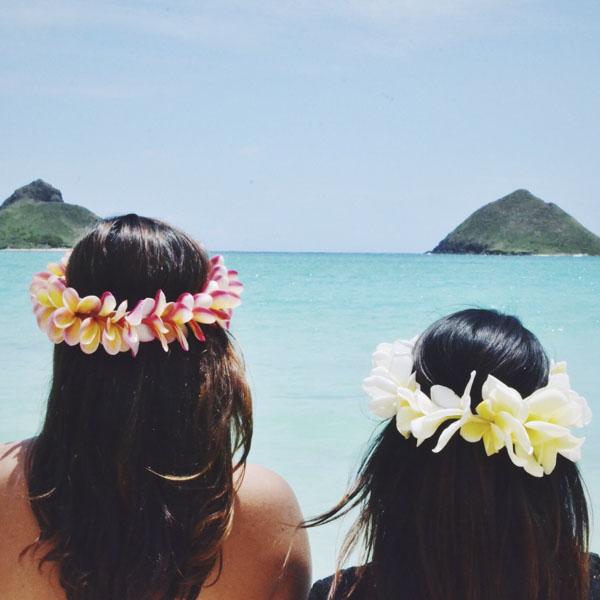 Girls wearing Haku lei in Hawaii looking at Mokulua Islands