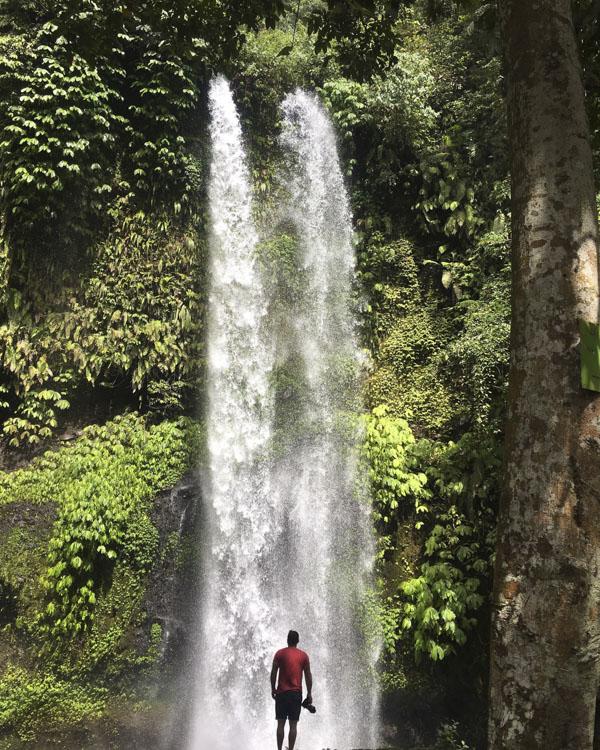 Man looking up at waterfall